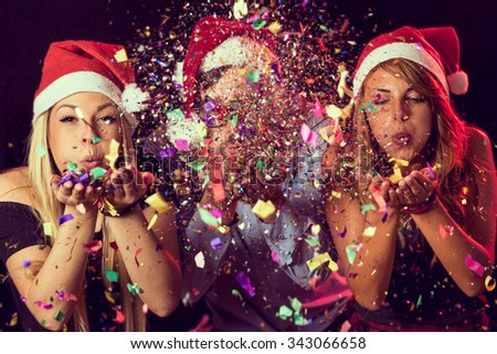 Three young people wearing Santa's hats, blowing colorful confetti at midnight at New Year's Eve party - stock photo