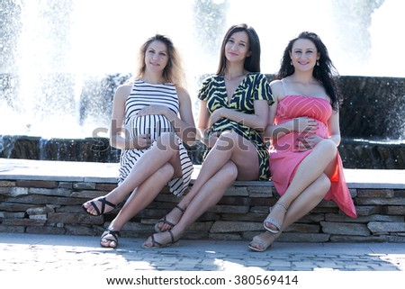 Three young pregnant women having fun against a fountain in the park.