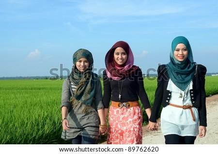 Three young pretty Asian muslim walk at paddy field - stock photo