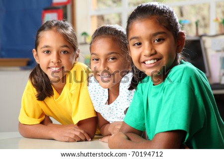 Three young primary school girls sitting in class