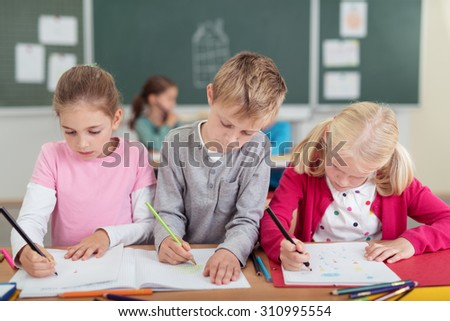 Three young primary school pupils working side by side at a desk in the classroom writing notes in their files - stock photo
