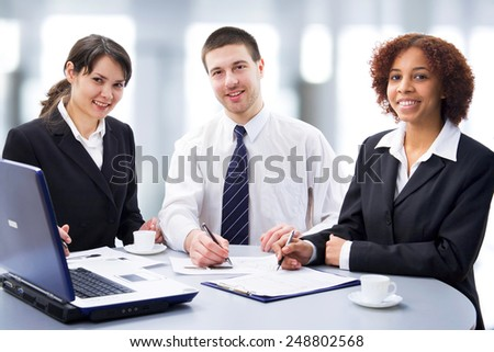 Three young professionals looking at camera  - stock photo