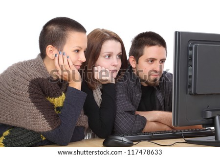 Three young relaxed Caucasian people looking to computer