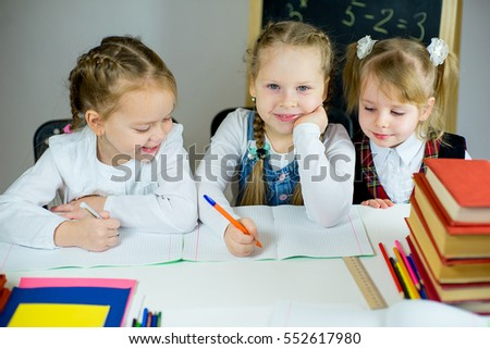 three young schoolgirls sitting at the table ready to learn. isolated on white background