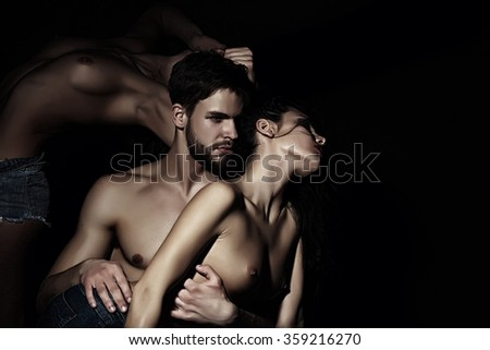 Three young sexy people of handsome bearded muscular macho man touching two sensual attractive girls lovers with beautiful body and naked chest close to each other indoor, horizontal picture - stock photo