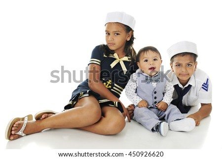 Three young siblings happily sitting in their sailor outfits.  On a white background. - stock photo