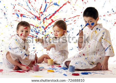 Three young siblings in paint-spattered white smocks, having fun painting in primary colors on white. - stock photo