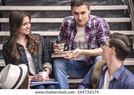 Three young students learning on stairs in college. - stock photo
