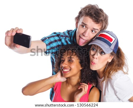 Three young teenagers taking a self portrait with a phone. Isolated on white background. - stock photo