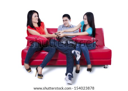 Three young teenagers watching television and fighting for remote control