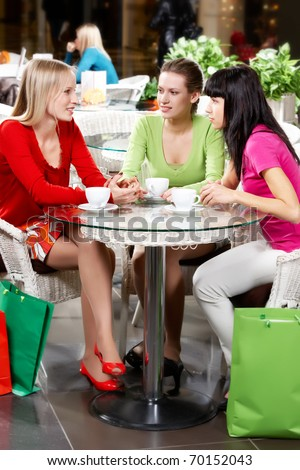 Three young woman drinking coffee in cafe