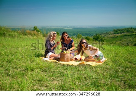 Three young woman eating on picnic at countryside and spending summer day in nature. - stock photo