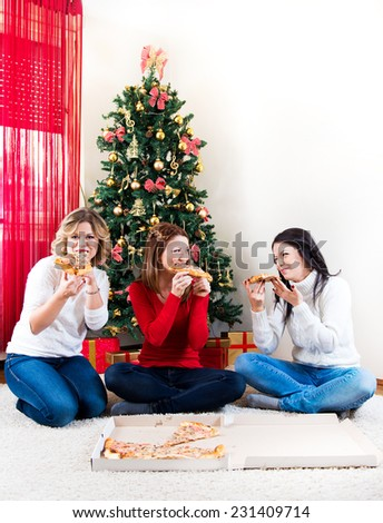 Three young woman eating pizza in front of Christmas tree - stock photo