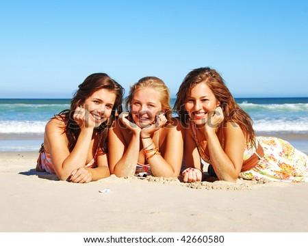 Three young woman enjoying summer on the beach - stock photo