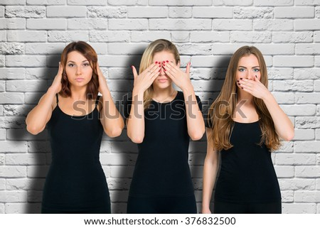 Three young woman in black clothes isolated at grey brick wall background showing blind, deaf and dumb: wise monkey scene - hear no evil, see no evil, speak no evil - stock photo