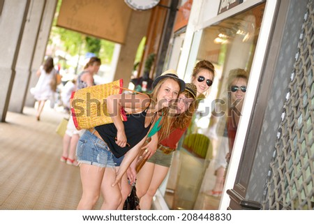 three young women are shopping in the city
