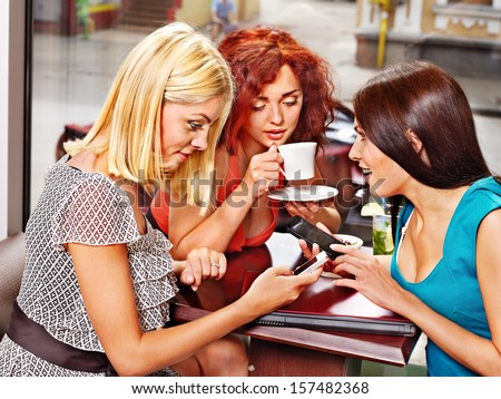 Three young women at laptop drinking coffee in a cafe. - stock photo