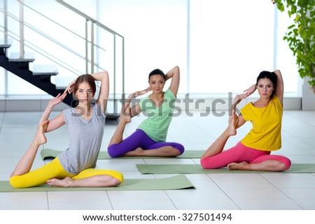 Three young women do yoga - stock photo