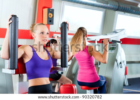 Three young women doing strength or sports training in gym for a better fitness - stock photo
