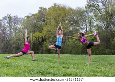 Three young women exercising at a local park - stock photo