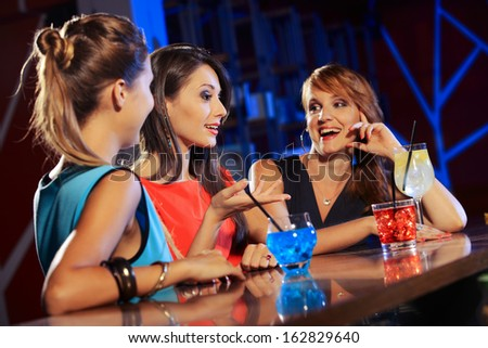Three young women having a drink and talking in a night club  - stock photo