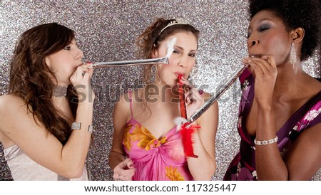 Three young women having a party and blowing whistles on each other, against a silver background.