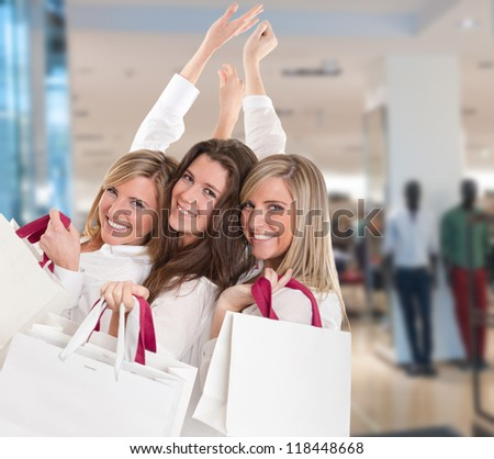 Three young women in a happy shopping expedition - stock photo