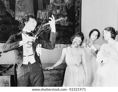 Three young women looking with adoration at a violin player - stock photo
