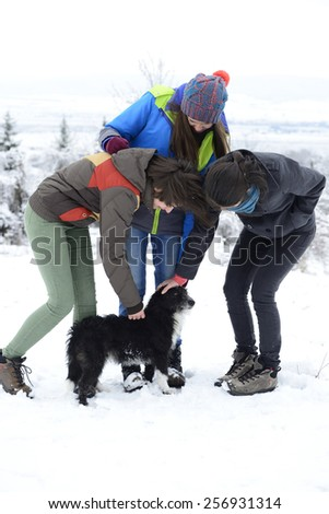 Three young women petting small black dog outside in winter. - stock photo
