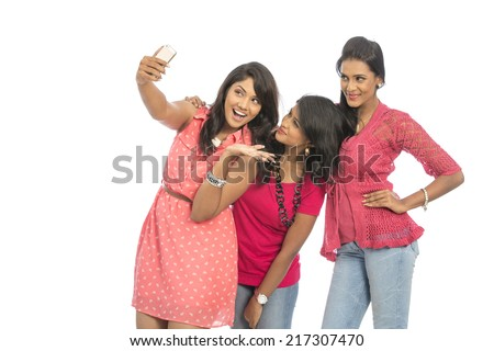 Three young women taking selfie with mobile phone  - stock photo