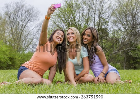 Three young women taking selfies and enjoying a day at the park - stock photo