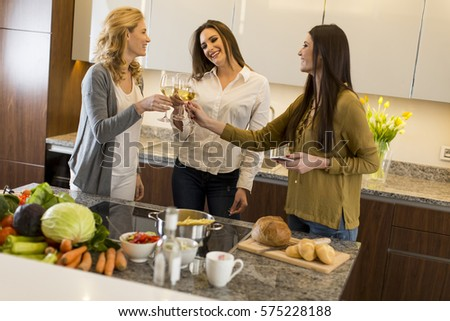 Three young women toasting with white wine