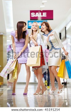 Three young women with bags laugh in shop