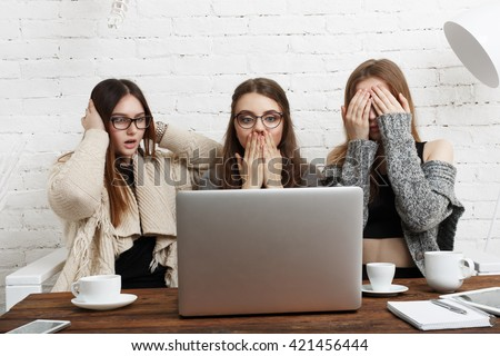 Three young women with computer showing blind, deaf and dumb: three wise monkey scene - hear no evil, see no evil, speak no evil. Girls look at monitor show indifference, negation, silence. - stock photo
