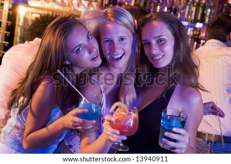 Three young women with drinks in a nightclub - stock photo