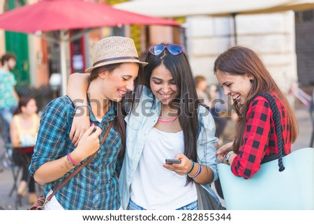 Three young women with smart phone in the city, talking and smiling. This is a mixed race group, one girl is half asian and one is middle eastern. Lifestyle, friendship and urban life concepts. - stock photo