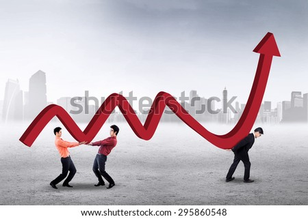 Three young workers carrying financial chart together outdoors, symbolizing a cooperation to increase business - stock photo