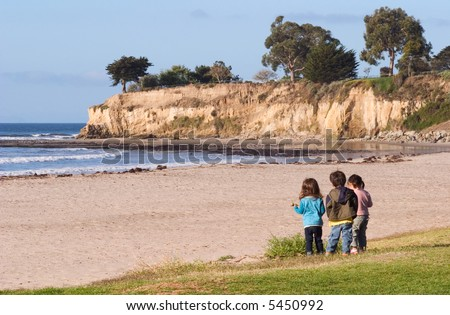 Three youngsters looking at the Pacific coastline and tide-pools in Santa Barbara, California. - stock photo