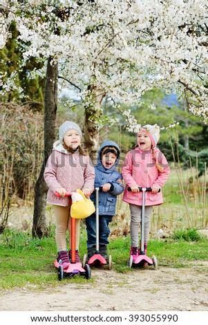 threee children on the scooters under the blossom tree - stock photo