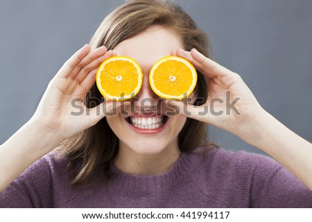 thrilled beautiful young woman with two zesty orange slices on her eyes for fun colorful and optimistic vision, indoors