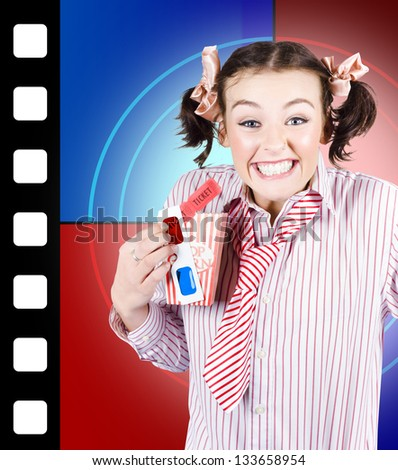 Thrilled dorky woman holding retro popcorn box and film tickets while standing in front of cinema screen at 3D movie premier - stock photo