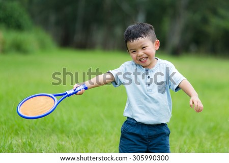 Thrilled Little kid play with tennis - stock photo