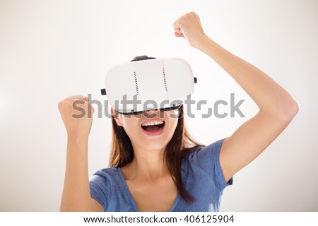 Thrilled Woman wearing virtual reality device - stock photo