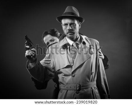 Thriller film noir scene with man pointing a gun and woman hiding behind him - stock photo