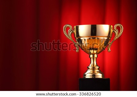 throphy in front of the red curtain - stock photo