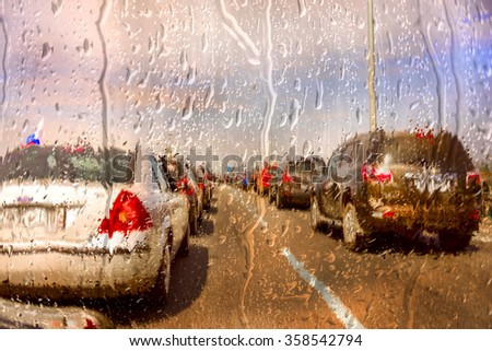 Through a car windshield during starting rain storm - stock photo
