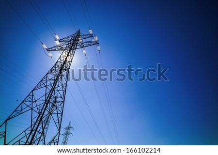 through a mast of a high voltage cable for electricity, the sun shines. solar energy - stock photo