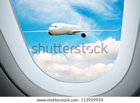 Through the aircraft windows, Large passenger plane flying in the blue sky - stock photo