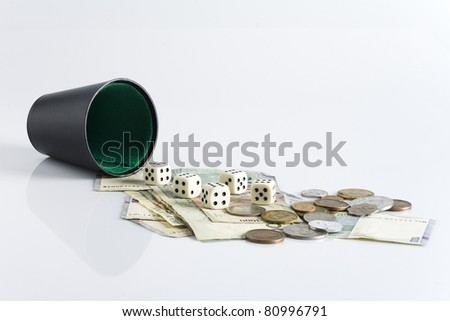 Throwing dice from a cup over some money - stock photo