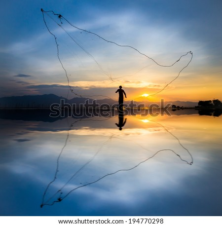 throwing fishing at sunset silhouette - stock photo